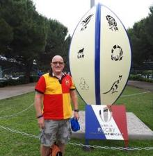 Man smiling next to a rugby ball statue